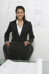 Asian businesswoman standing near architectural drawings