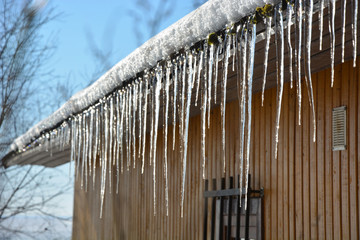 Icicles on the roof at the sunny winter day