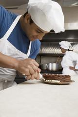 Hispanic male pastry chef decorating cake
