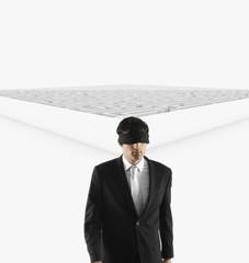 Blindfolded European businessman in front of maze