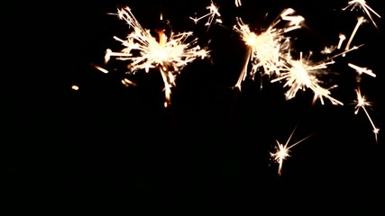 Person`s hand sets fire and holding sparklers on black