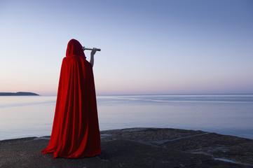 Caucasian woman with telescope overlooking ocean