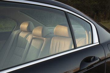 The leather backseat of a car viewed through side window