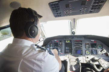 Caucasian pilot working in airplane cockpit