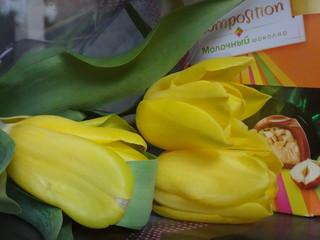Желтые тюльпаны рядом с коробкой с шоколадными конфетами