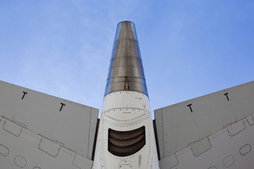 Low angle view of airplane tail against blue sky