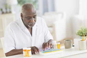 Black man counting pills in pill boxes