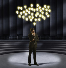 European businessman standing under floating light bulbs