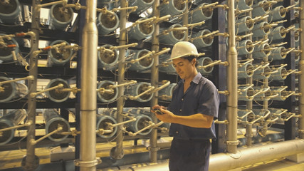 Hispanic worker with cell phone in warehouse