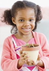 Mixed race girl holding seedling in pot