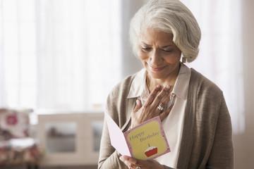 Older African American woman reading birthday card