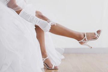Hispanic bride pulling on garter