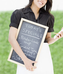 Asian waitress holding chalkboard with day's specials