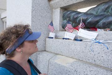 woman looking at memorial for fallen veteran