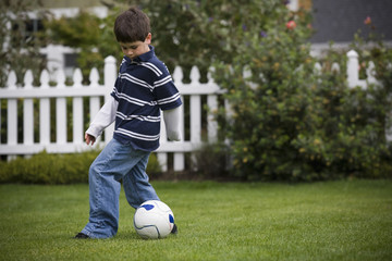 Mixed race boy playing soccer in backyard