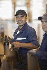 Hispanic men working in bottling factory