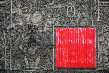 Balinese stone carving background with the red square shield
