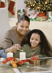Mixed Race mother and daughter lighting Christmas candles