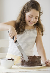 Hispanic girl icing cake