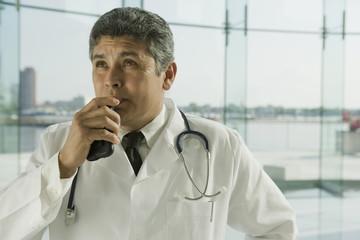 Hispanic doctor in lab coat speaking into dictaphone