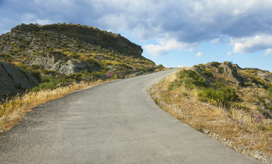 An empty road leading uphill in the middle of the Tabernas desert