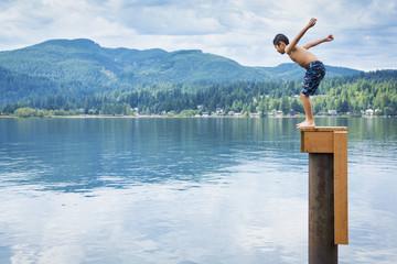 Korean boy jumping off platform into lake