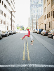 Hispanic teenage boy doing back flip in urban street