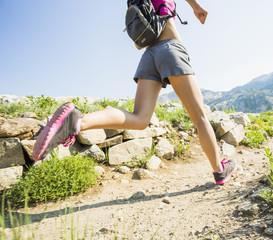 Caucasian woman running on rocky trail