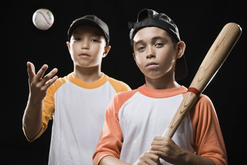 Boys holding bat and throwing baseball