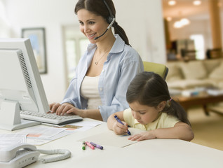 Woman in headset typing on computer with daughter nearby