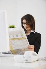 Hispanic businesswoman reading newspaper