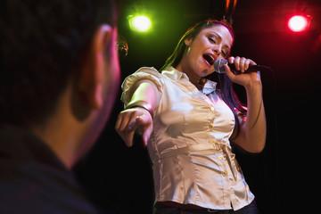 Hispanic woman singing in nightclub
