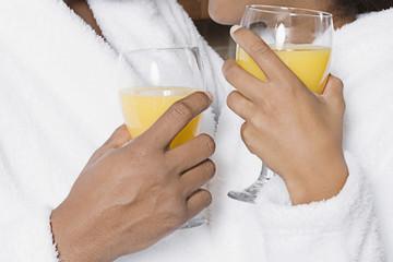 African couple holding orange juice