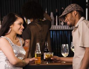 Multi-ethnic couple drinking in nightclub