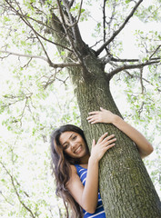 Middle Eastern woman hugging tree
