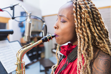 African American saxophone player recording in studio