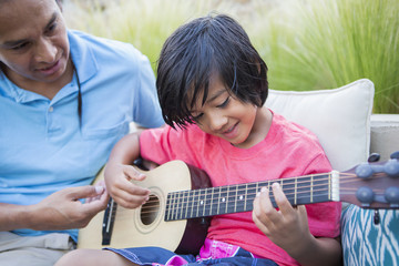 Father teaching son to play guitar outdoors