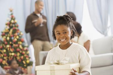 African girl holding Christmas gift