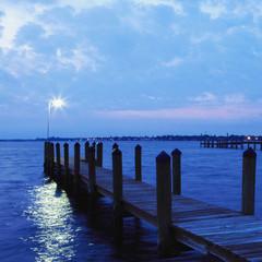 Illuminated lamp at edge of dock on lake at dusk