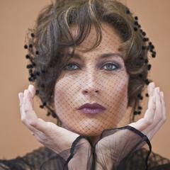 Glamorous Hispanic woman with netting across face