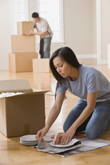 Asian couple packing moving boxes