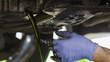 Leinwanddruck Bild - Mechanic draining oil from a car