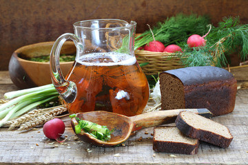 Jug with kvass, rye bread and greens with a garden radish in a b
