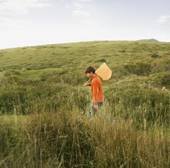 Hispanic boy carrying net in field