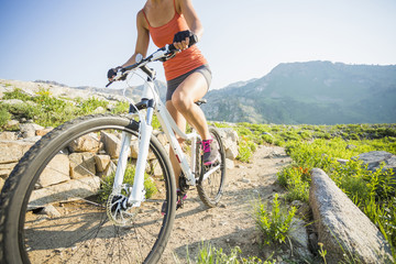 Caucasian woman riding mountain bike on rocky trail