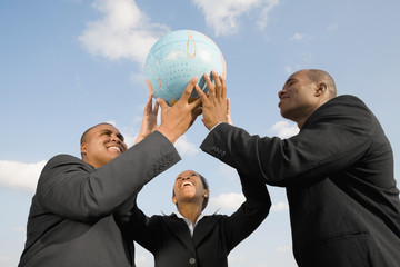 African businesspeople holding up globe