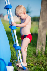 Boy standing on swimming pool stairs