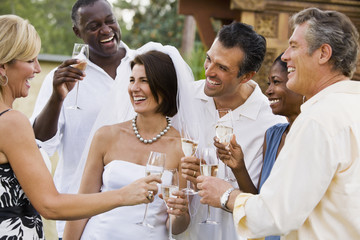 Multi-ethnic friends toasting newlyweds