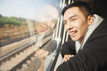 Chinese man looking out train window