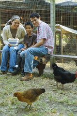 Multi-ethnic family holding bowl of eggs next to chickens